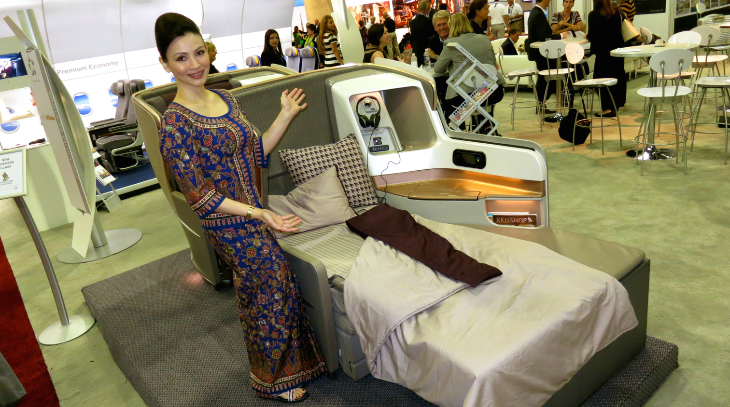 A Singapore Girl shows off Singapore Air's new business class seat now appearing on its 777s (Chris McGinnis)