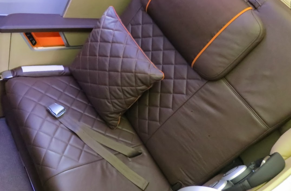 Singapore Air's new first class seat in chocolate brown leather trimmed in bright pumpkin orange (Chris McGinnis)
