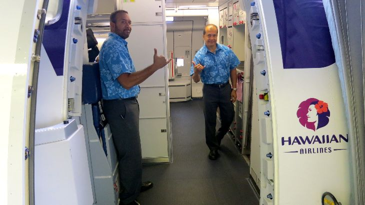 Male cabin crew sharply dressed in teal aloha shirts and pressed gray slacks (Photo: Chris McGinnis)